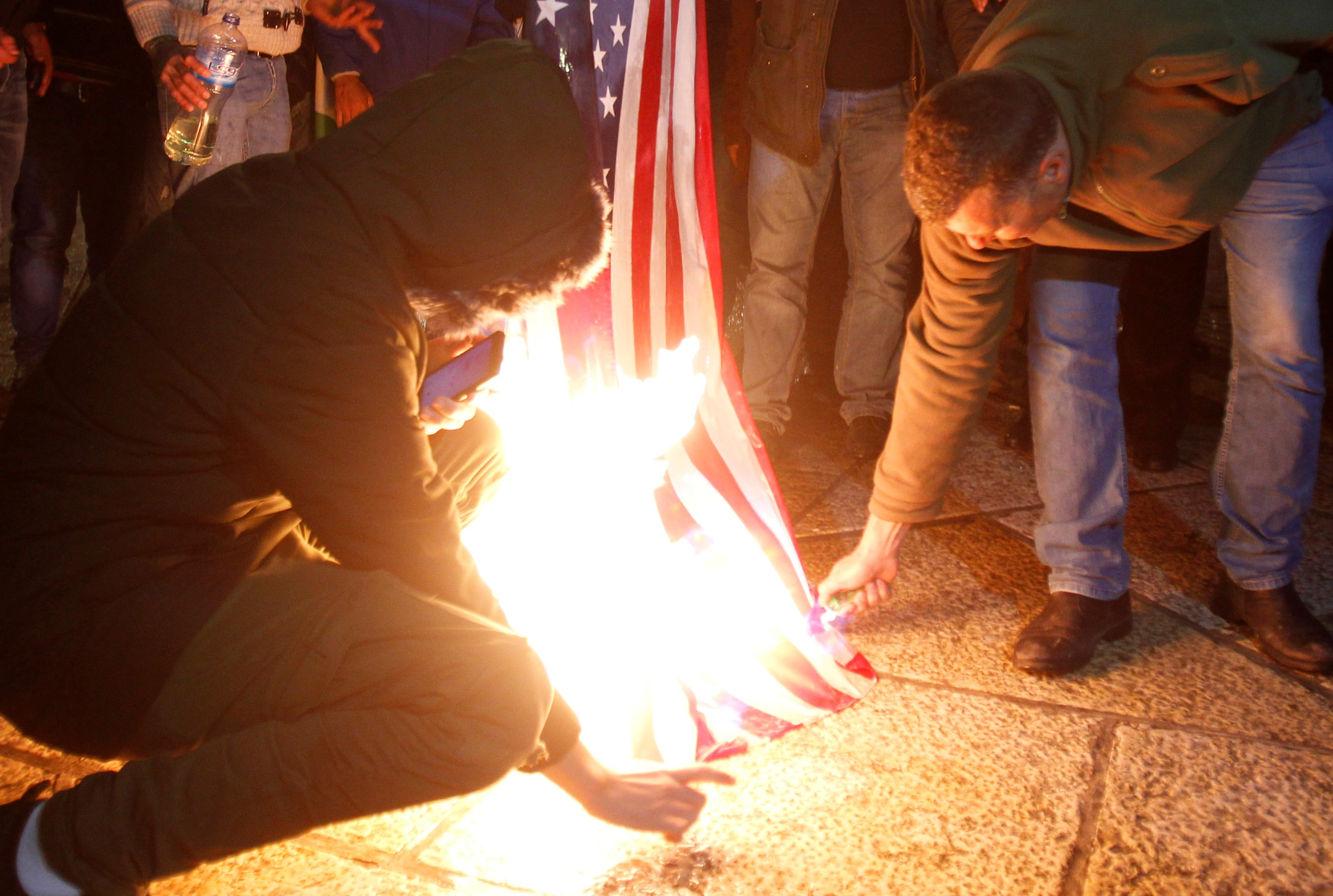 Palestinian demonstrators burn the US flag in Bethlehem's Manger Square in protest to the declaration of the US president declaring Jerusalem as Israel's capital on December 6, 2017. Abbas said the United States can no longer play the role of peace broker after Donald Trump's decision on Wednesday to recognise Jerusalem as Israel's capital. / AFP PHOTO / Musa AL SHAER